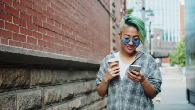 vídeos de stock, filmes e b-roll de movimento lento da mulher consideravelmente asiática que anda ao ar livre com café e smartphone - moda hipster