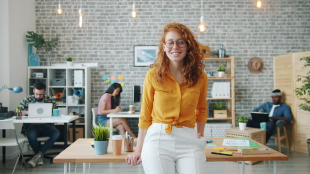 Slow motion of pretty smiling girl standing in office looking at camera Slow motion of pretty smiling girl standing in office looking at camera while people multi-ethnic team are working in background. Youth and business concept. redhead stock videos & royalty-free footage