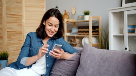 vidéos et rushes de ralenti de jolie femme souriant obtenant de bonnes nouvelles regardant le smartphone - jeunes femmes
