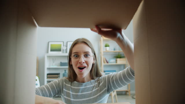 ポジティブな感情を表現するかわいい若い女性のオープニングボックスのスローモーション - プレゼント点の映像素材/bロール