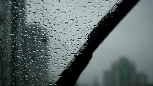 Slow motion of rainy day view during car windshield wipers rain drops sliding down inside a car video
