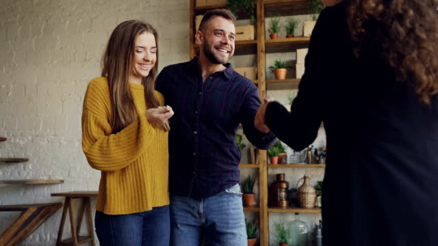 Slow motion of real estate buyers getting keys from housing agent after successful deal, kissing and hugging with happiness and shaking hands to female broker.