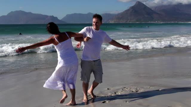 rallentatore di filatura in coppia romantica sulla spiaggia, città del capo, sudafrica - quarantenne video stock e b–roll