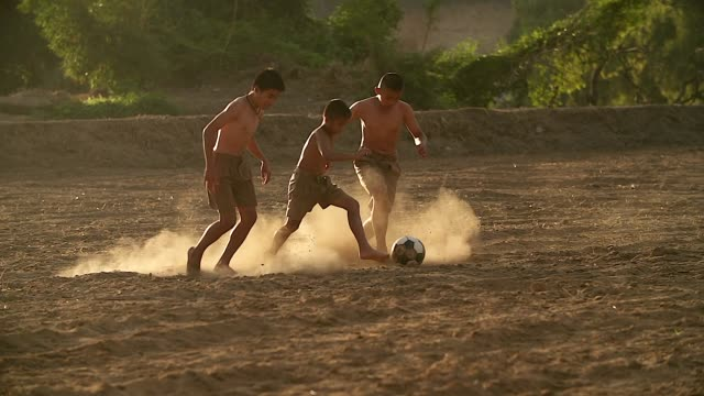 vídeos de stock e filmes b-roll de slow motion of rural children are playing football in the sunshine day in a village. - cultura tailandesa
