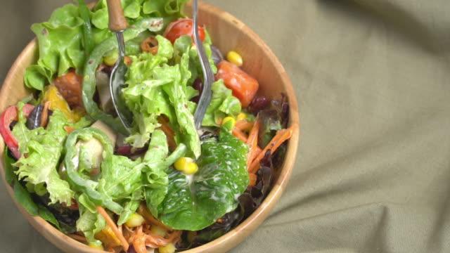 vídeos de stock e filmes b-roll de slow motion of scooping mixing salad bowl. - saladeira