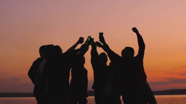 slow motion of silhouette group young dancing people cheers and have a party at beach on sunset - alchol video stock e b–roll