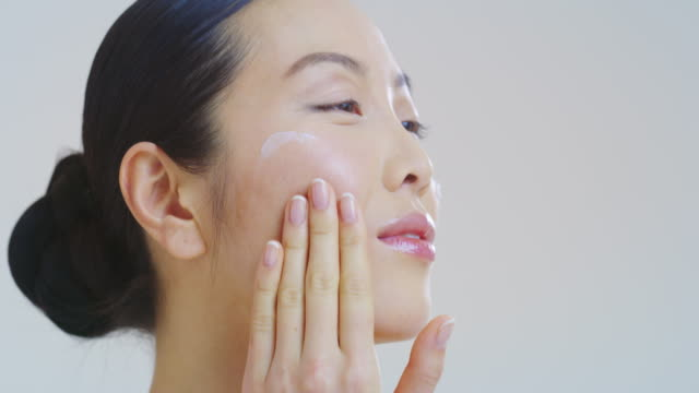 Slow motion of smiling beautiful asian woman with perfect skin just cleaned from impurities gently applying on face with fingers day or night cream Slow motion of smiling beautiful asian woman with perfect skin just cleaned from impurities gently applying on face with fingers day or night cream. serum sample stock videos & royalty-free footage