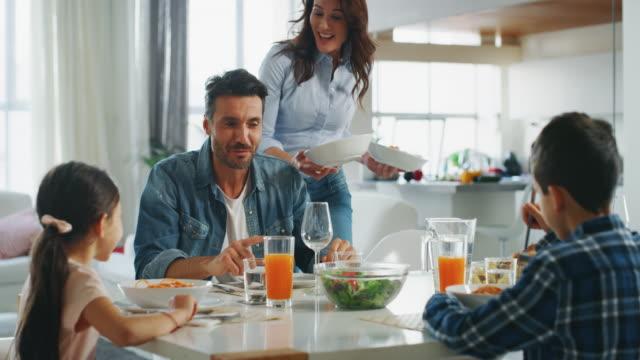 vídeos de stock, filmes e b-roll de movimento lento da matriz de sorriso que sere uma família com almoço na sala de jantar. - comer