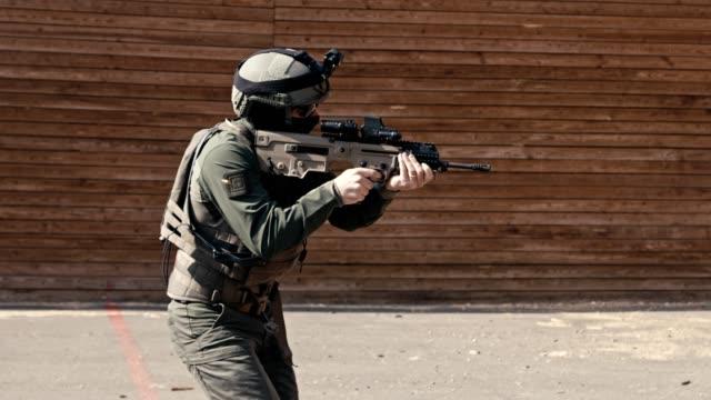 vidéos et rushes de mouvement lent du soldat tirant le fusil automatique dans une gamme - mitrailleuse