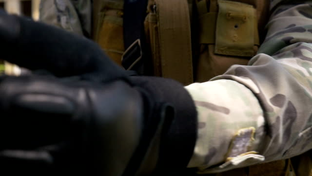 Slow motion of soldier tightening military gloves for better holding his riffle gun preparing for shooting video