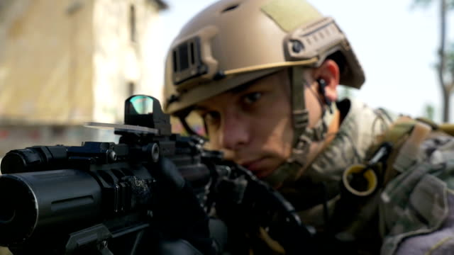 Slow motion of soldier with gun and headset aiming target in tactical operation ready for firing video