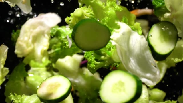 Slow motion of Splashing Green Salad flying up to camera