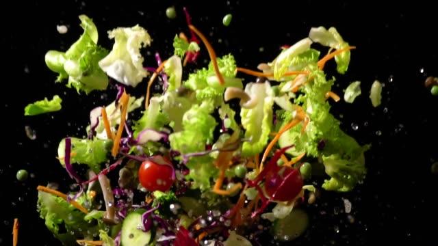 slow motion of splashing salad flying up - sałata filmów i materiałów b-roll