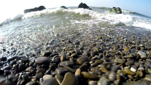 Slow motion of splashing waves on a wild pebble beach video