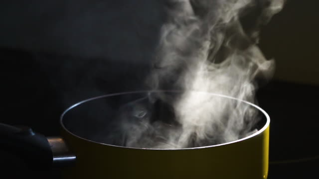 Slow motion of Steam in cooking pot Steam in cooking pot with black background cooking pan stock videos & royalty-free footage