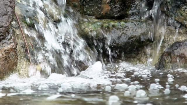 Slow Motion of stream river running over mossy rocks. Mountain river forest