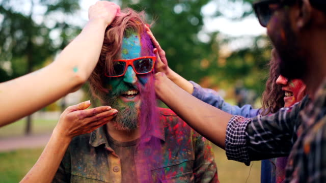 vídeos de stock e filmes b-roll de slow motion of students dying bearded guy's face and hair with multicolor powder paint during holi party outdoors, young man in sunglasses is laughing. - holi