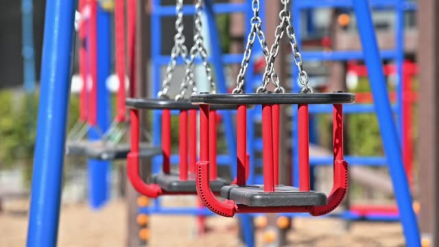 slow motion of swings at empty children playground in residential area of chisinau, moldova during covid-19 virus threat - молдавия стоковые видео и кадры b-roll