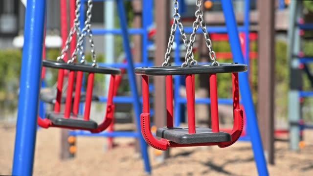 slow motion of swings at empty children playground in residential area - молдавия стоковые видео и кадры b-roll