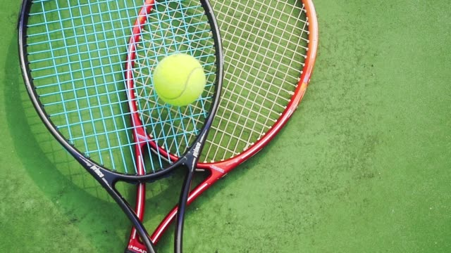 Slow motion of tennis professional rackets and yellow ball lying on green field of court. 1920x1080 video