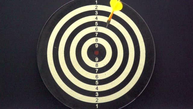 Slow motion of throwing darts at the target, concept of achieving the goal.