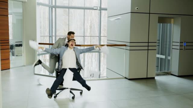 vídeos de stock, filmes e b-roll de câmera lenta de dois empresários loucos andando de cadeira de escritório e jornais a vomitar enquanto se diverte no átrio do centro de negócios moderno - festa da empresa