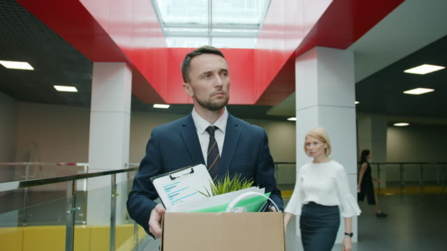 Slow motion of unhappy young man leaving work with box of things after dismissal video