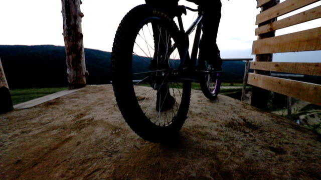 Slow motion of unrecognizable cyclist spinning back wheel of his mountain bicycle on dirt ground. video