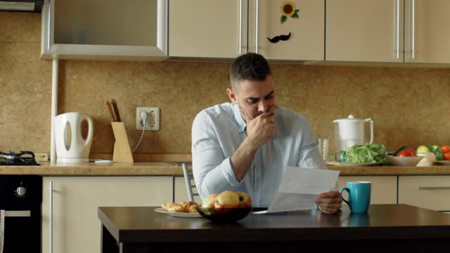 vídeos de stock e filmes b-roll de slow motion of upset young man reading letter with unpaid bill in the kitchen at home - carta documento