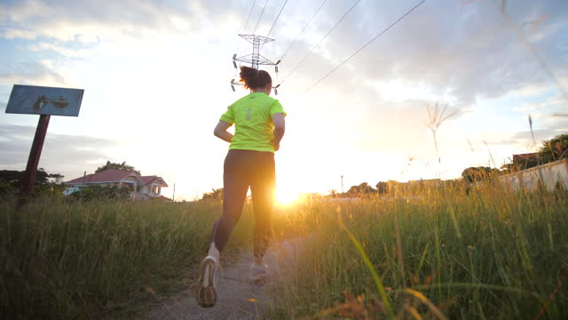 Slow motion of Woman exercise by Running on the way in park at dusk time