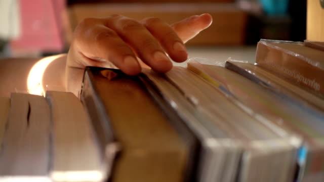 stockvideo's en b-roll-footage met slow motion van vrouw hand een boek op boekenplank vinden in de bibliotheek - boekenkast