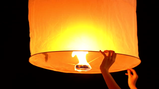 slow motion of woman hand holding sky lantern in loi krathong and yi peng traditional festival, chiang mai, thailand - sky lantern stock videos and b-roll footage