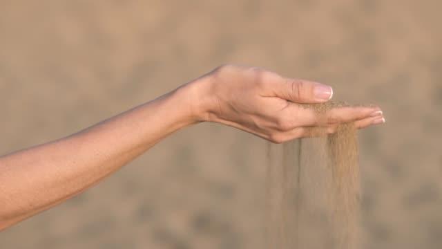 vídeos de stock e filmes b-roll de slow motion of woman hand pouring sand through fingers at the beach. - mulher deixar ir