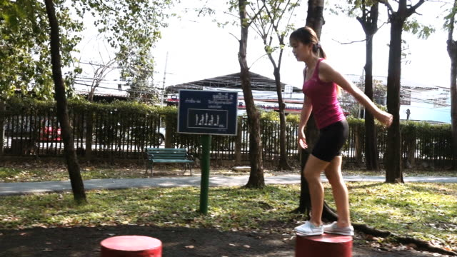 Slow Motion Of Woman Jumping On The Red Block Shape In Public Park video