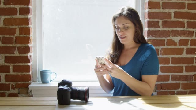 Slow motion of woman sending a text with professional camera on table video