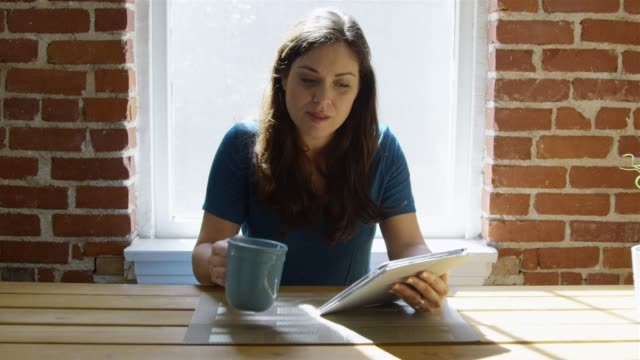 Slow motion of woman using tablet , drinking coffee and smiling video