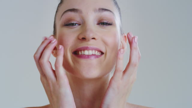 Slow motion of woman with beautiful face and perfect skin just cleaned from impurities touching it gently with hand to show how soft and smooth it is Slow motion of woman with beautiful face and perfect skin just cleaned from impurities touching it gently with hand to show how soft and smooth it is. serum sample stock videos & royalty-free footage