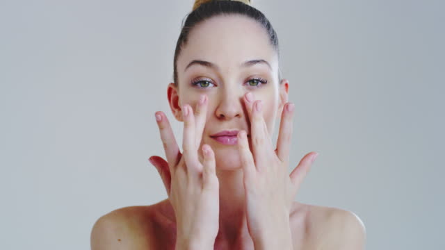 Slow motion of woman with beautiful face and perfect skin just cleaned from impurities pampering it gently with fingers to prepare for day or night cream Slow motion of woman with beautiful face and perfect skin just cleaned from impurities pampering it gently with fingers to prepare for day or night cream. serum sample stock videos & royalty-free footage