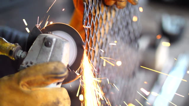 Slow Motion of Worker Using Machine Cutting Net Metal with Sparking