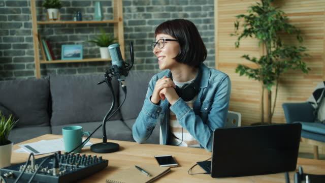 vídeos de stock, filmes e b-roll de movimento lento do podcast novo da gravação da mulher adulta para o blogue audio - podcast