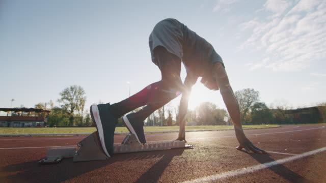 il rallentatore del giovane atleta africano sta lanciando la linea di partenza in una gara nello stadio di atletica leggera - atletico video stock e b–roll