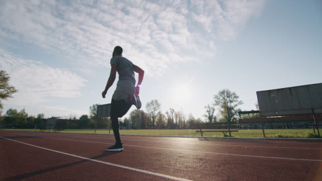 Slow motion of young african male athlete is running on race track in athletics stadium