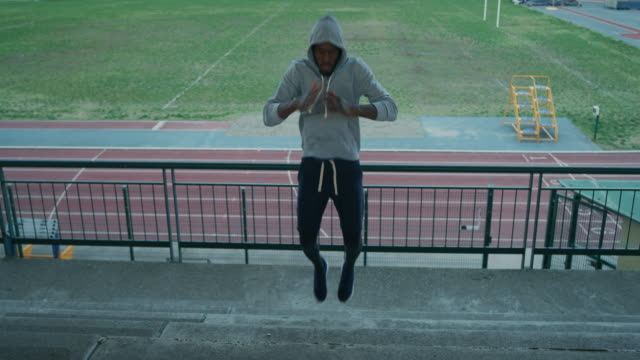 slow motion of young african male athlete is warming up for start the training race in athletics stadium - rozgrzewka filmów i materiałów b-roll