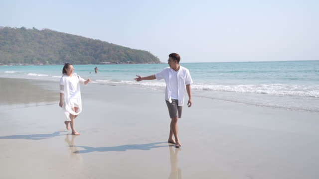 HD Slow motion of young Asian couple man and woman holding hands and walking together on the beach with smiling. Happy family husband and wife relax and enjoy with romantic summer holiday vacation.