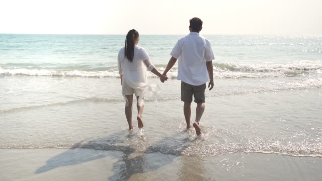 HD Slow motion of young Asian couple man and woman holding hands and walking together with smiling on the beach at sunset. Happy family husband and wife relax and enjoy with romantic summer vacation.