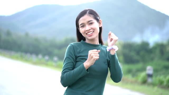 vidéos et rushes de le mouvement lent de la jeune femme asiatique apprécient et dansant la nature. - bras humain