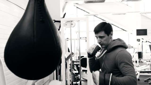 スポーツ フィットネス クラブでサンドバッグで練習若いボクサー男のスローモーション ビデオ