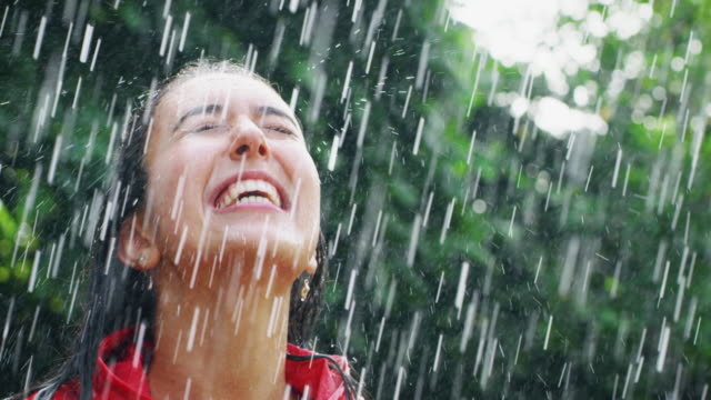 vídeos de stock e filmes b-roll de slow motion of young carefree beaoutiful woman wearing protection cape is feeling free under the rain on a background of green trees - water born nature