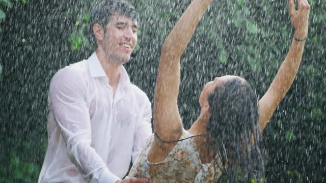 il rallentatore di una giovane coppia spensierata innamorata si abbraccia e si bacia sotto la pioggia su uno sfondo di alberi verdi - romanticismo concetto video stock e b–roll