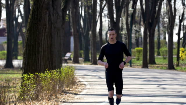 Slow motion of young fit sportive catching breath after jogging in the park video